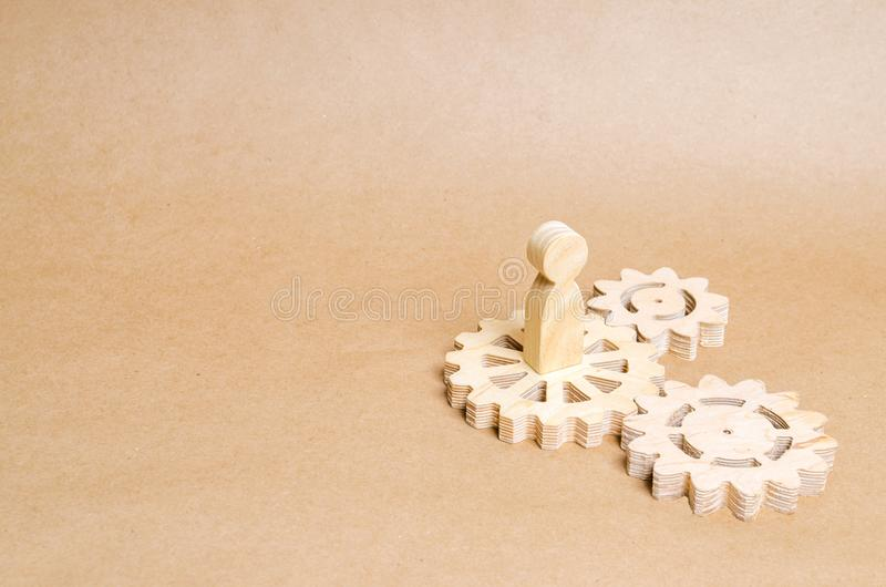 The person stands on a wooden gear. The concept of technology and industry, the think process. Part of a large complex mechanism. Business process, institution stock images