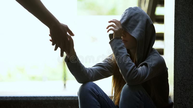 Person stretching helping hand to lonely depressed teen girl, support and aid. Stock photo stock photos