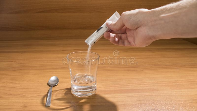 A person is taking an effervescent drug on a wood table royalty free stock photo