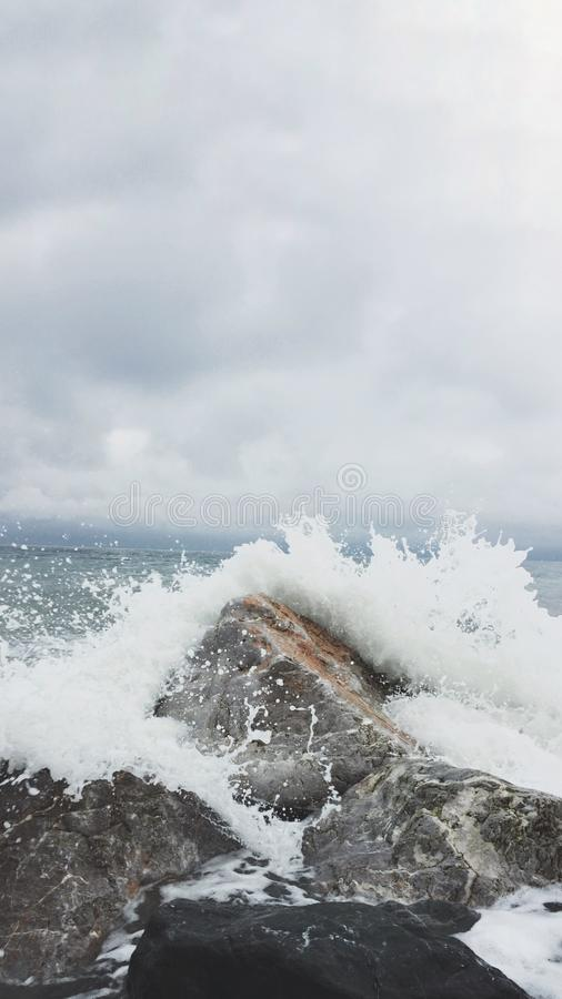 Person Taking Photo of Sea Waves and Gray Concrete Rock stock image