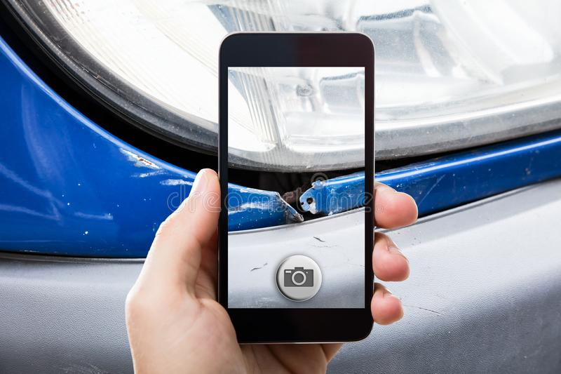 Person Taking Picture Of een Beschadigde Auto royalty-vrije stock afbeelding