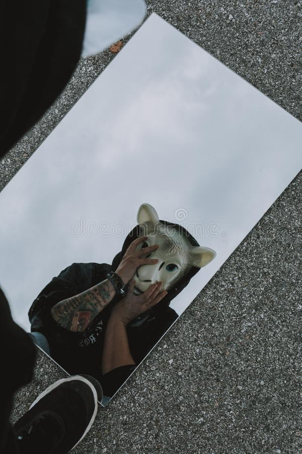 Person with tattoos wearing a sheep mask and black hoodie looking through a mirror on the ground stock photo