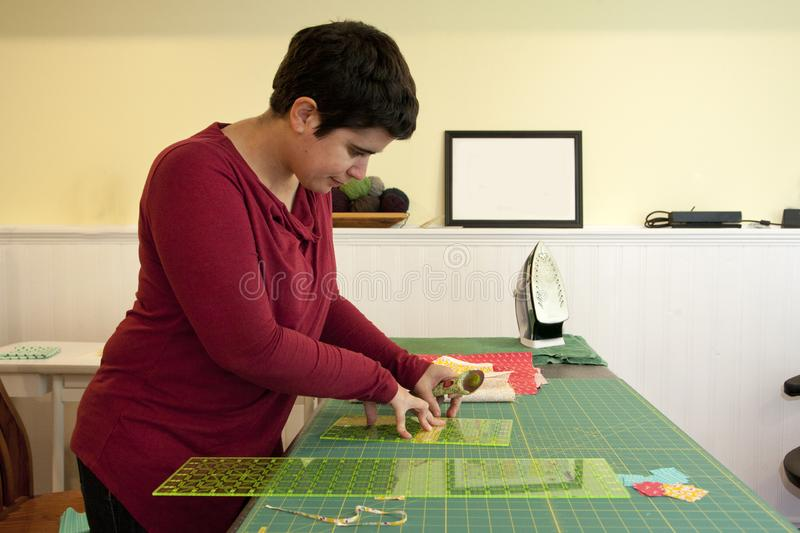 Person in their craft room measuring. Woman using a fabric cutter and measuring tools to make small strips stock images