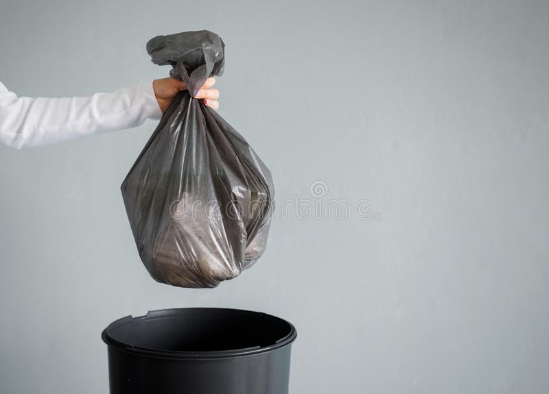 Person throwing out garbage in plastic bag stock images
