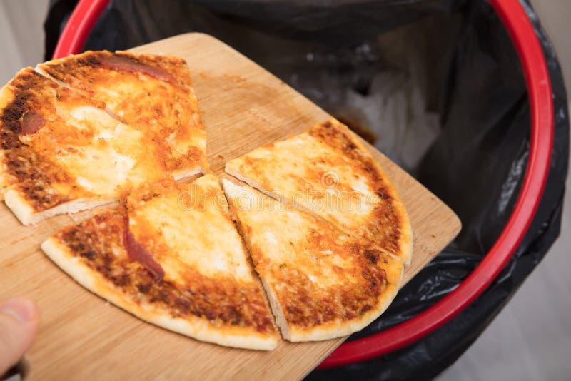 Person Throwing Pepperoni Pizza In-Vuilnisbak royalty-vrije stock fotografie