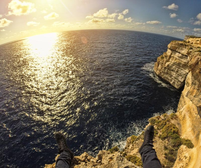 Person on Top of Stone Island in Front of Sea during Sunset stock photography