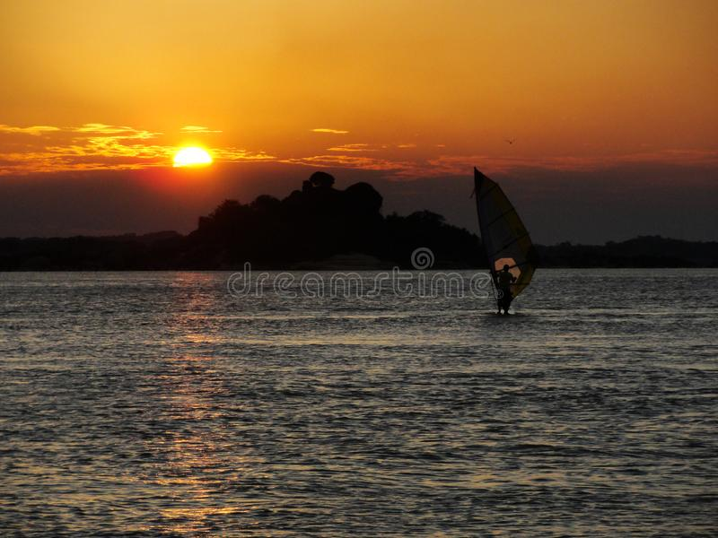 Person training windsurf in the holidays with the sunset in the background royalty free stock image