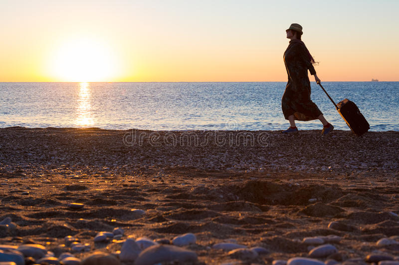 Person traveling Woman walking on Ocean Beach at Sunrise royalty free stock photos