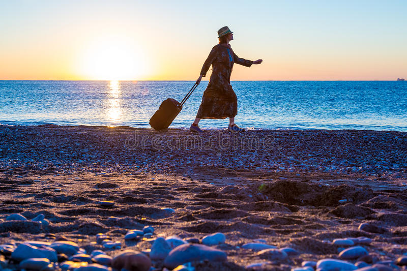 Person traveling Woman walking on Ocean Beach at Sunrise stock image