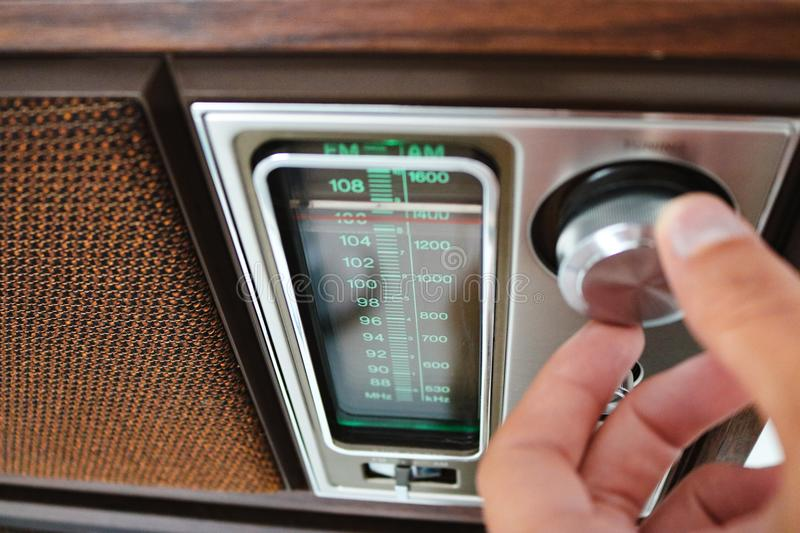Person Tuning an Old Fashioned Radio. Person turning the knob to tune a station on a retro radio stock photos