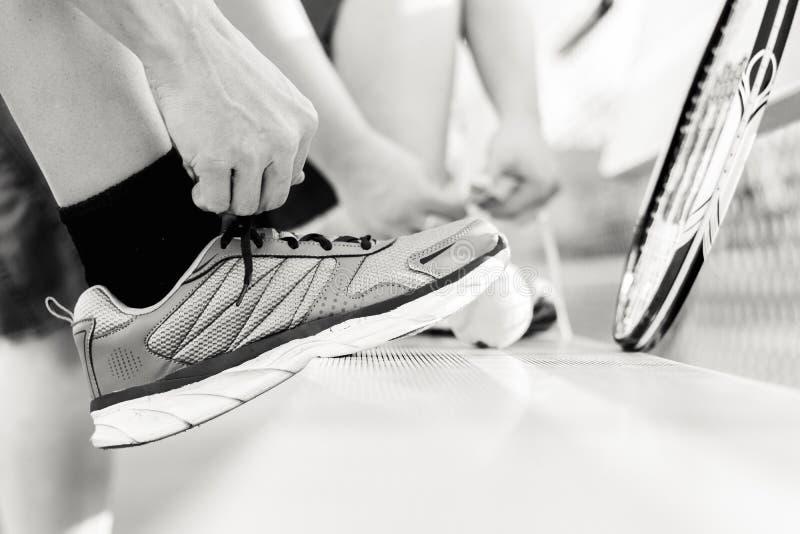 Person Tying His Shoe vor einem Spiel von Tennis lizenzfreies stockfoto