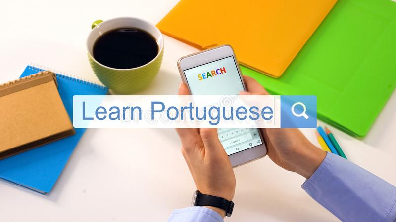 Person typing learn Portuguese phrase on smartphone search bar, education. Stock photo stock photo