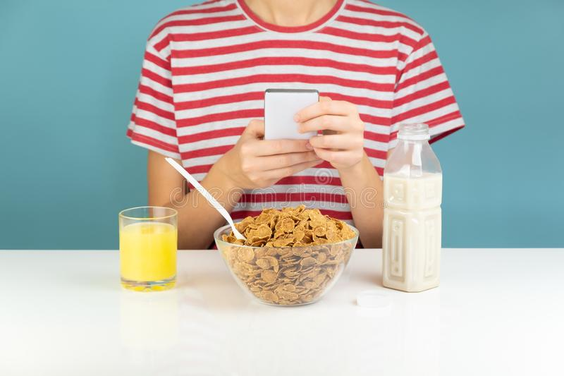 Person uses phone at breakfast table, minimalistic illustrative. Concept. Browsing social media while eating healthy whole grain cereal with juice and milk stock photography