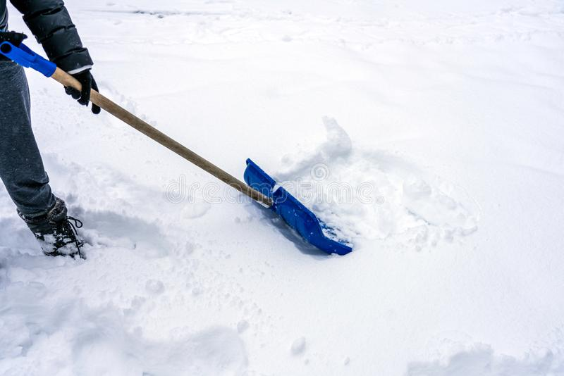 Person are using a Blue snow shovel/spade outdoors removing the deep snow during snowy weather. Climate and season concept royalty free stock images