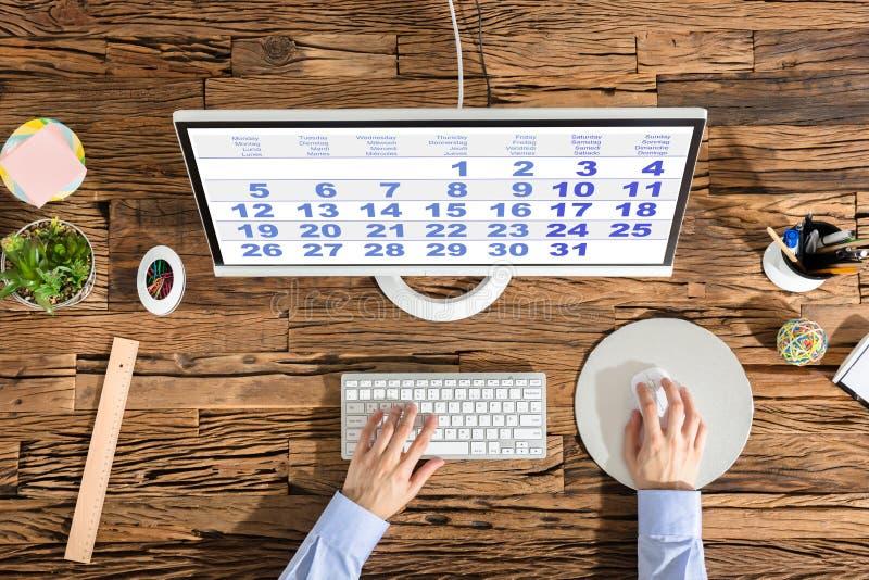 Person Using Computer With Calendar på skärmen arkivfoton