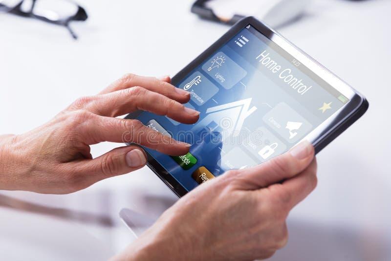 Person Using Home Control System en la tableta de Digitaces fotografía de archivo libre de regalías