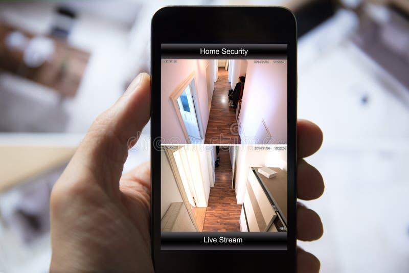 Person Using Home Security System på mobiltelefonen arkivfoton