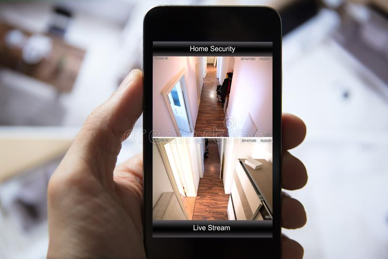 Person Using Home Security System sul telefono cellulare fotografie stock