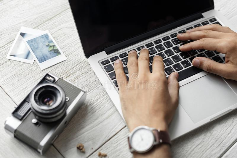 Person Using Macbook Pro Beside Grey Camera on Table royalty free stock photo