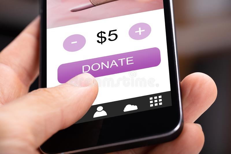 Person Donating Money On Cellphone stock photography