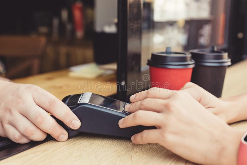 Person using pos terminal at the cafe. Person using pos terminal at the outdoor cafe royalty free stock images