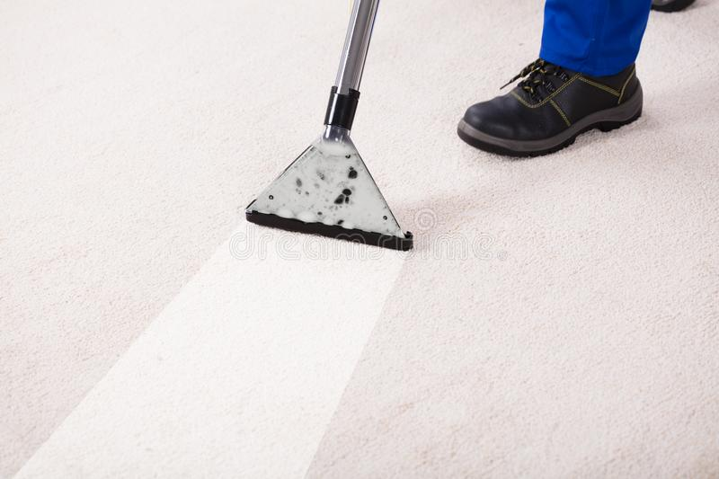 Person Using Vacuum Cleaner For Cleaning Carpet stock images