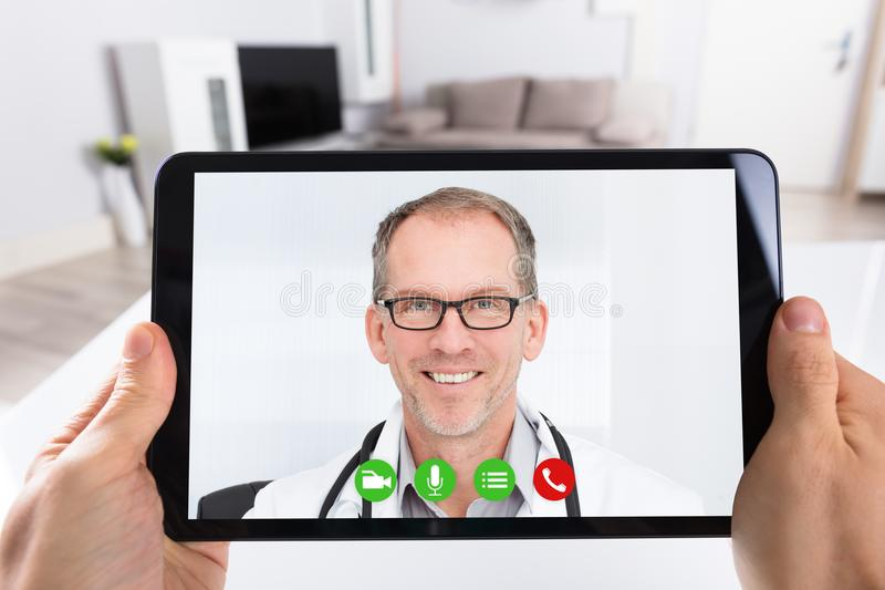 Person Video Conferencing With Doctor auf Digital-Tablet lizenzfreie stockfotos