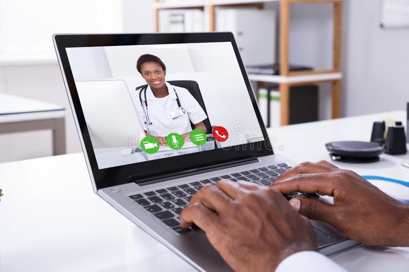 Person Video Conferencing With Female Doctor Through Laptop royalty free stock photos