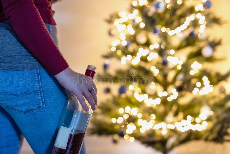 Person vor dem Weihnachtsbaum mit einer Flasche Alkohol, zu viel trinken während der Weihnachtszeit und Neujahr, stockfotos
