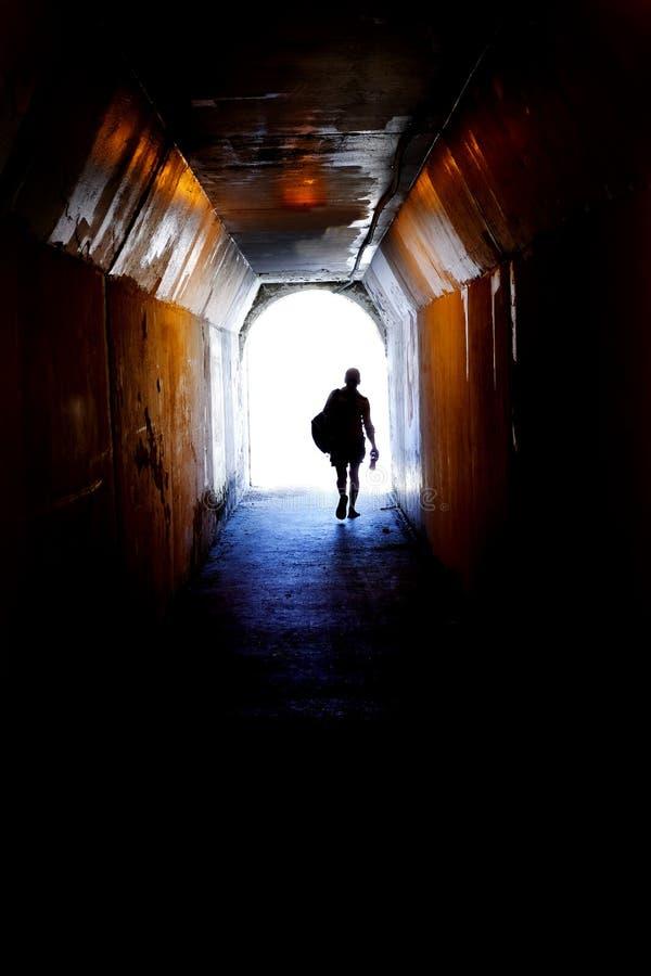 Person Walking à l'extrémité du tunnel vers la lumière symbolique photographie stock libre de droits