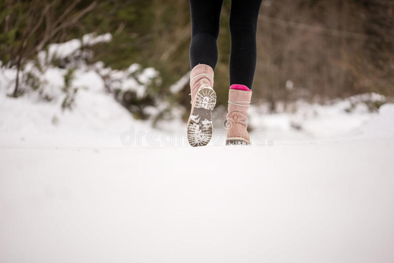 Person walking through snow wearing boots. Person walking away from the camera through white winter snow wearing boots in the countryside, low angle view of the stock photo