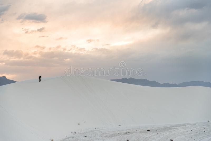 A person walking on a sand dune at White Sands National Monument in Alamogordo, New Mexico. A person walking during sunset at White Sands National Monument in stock photography