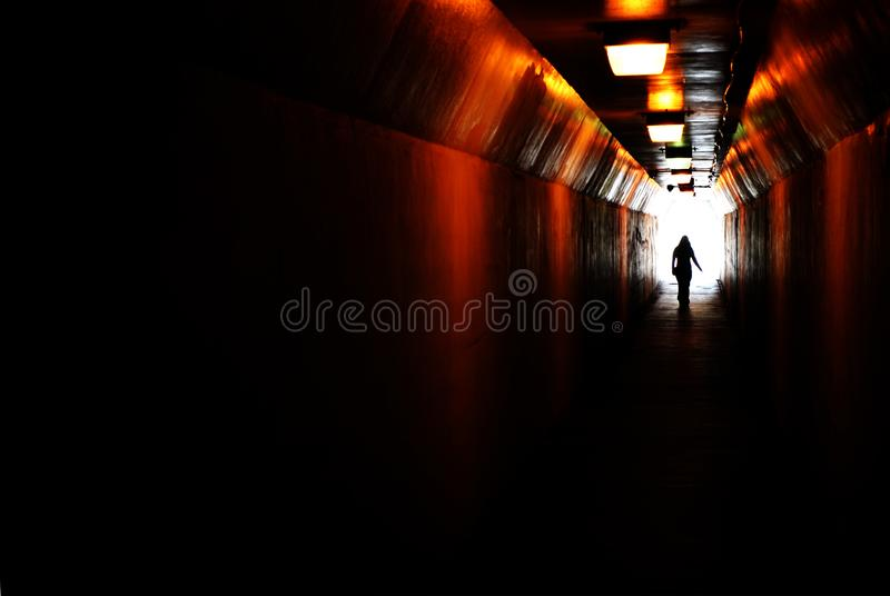 Person walking through tunnel towards light at end. Accomplishing goal or leaving darknenss for light stock image