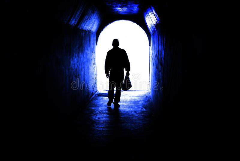 Person walking through tunnel towards light at end. Accomplishing goal or leaving darknenss for light stock photos