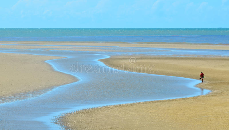 A person walks along a stream on a wild beach in Queensland Au royalty free stock photography
