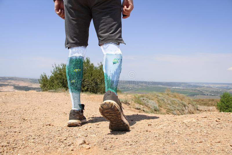 Person walks using glass legs in which fishes swims. Person walks on the hill far away from the city. View on transparent glass legs in which aquarium fishes stock images