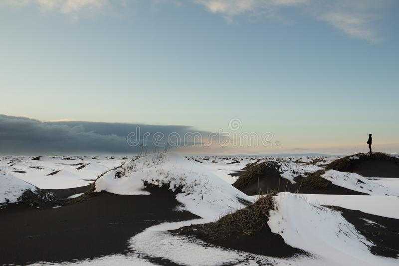 Person watching an approaching storm from a snow covered black s. Dark clouds build in the distance over snow covered black sand dunes near Vik, Iceland on the royalty free stock images