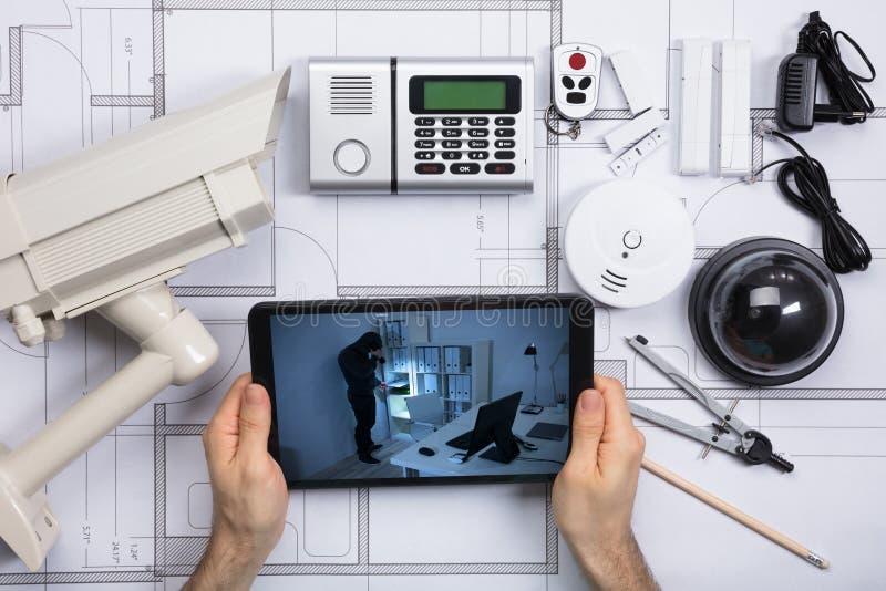 Person Watching Viewed Security Camera på mobiltelefonen arkivbild