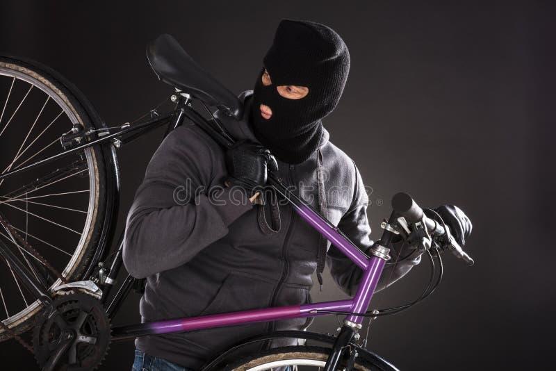 Person Wearing Balaclava Stealing una bicicleta fotos de archivo libres de regalías