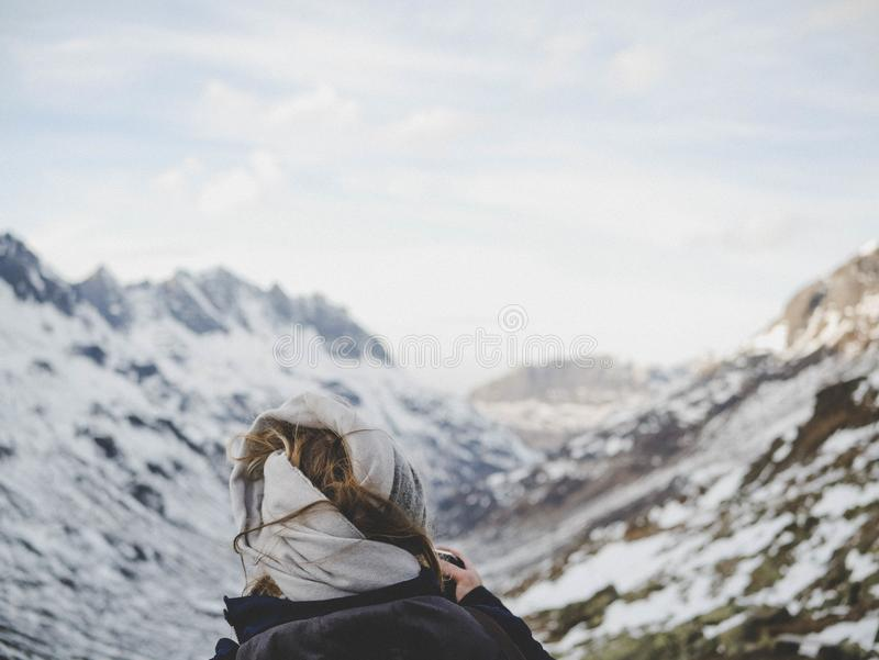 Person Wearing Black Jacket in Front of Mountain Filled With Snow stock images