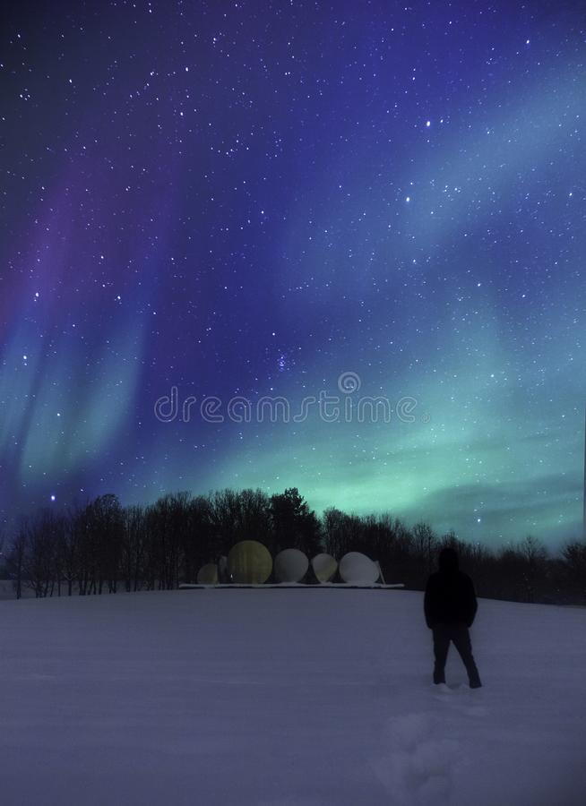 Person Wearing Black Jacket Standing on Snowy Field during Nighttime royalty free stock photography