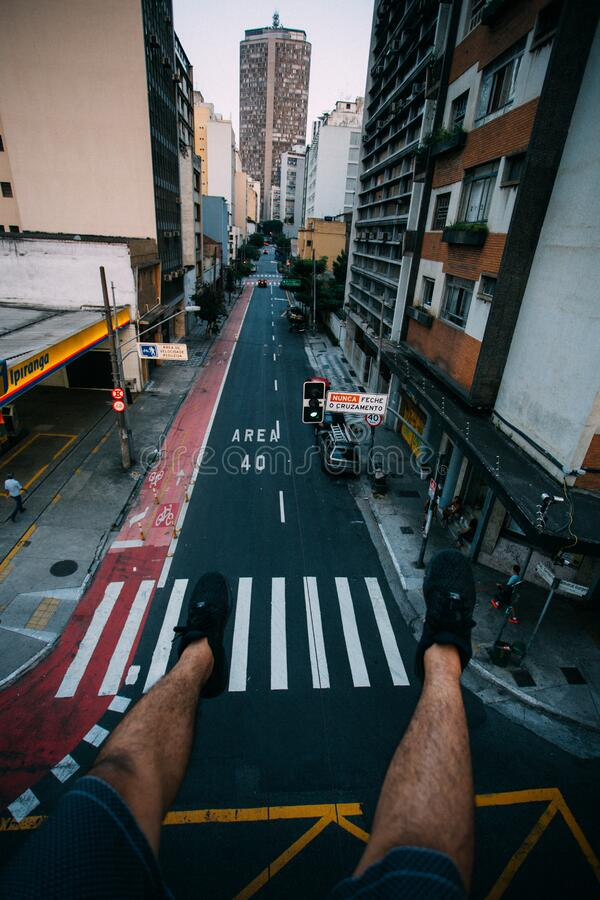 Person Wearing Black Lace Up Sneakers Facing Gray Concrete Road Top Between Concrete Buldings Free Public Domain Cc0 Image
