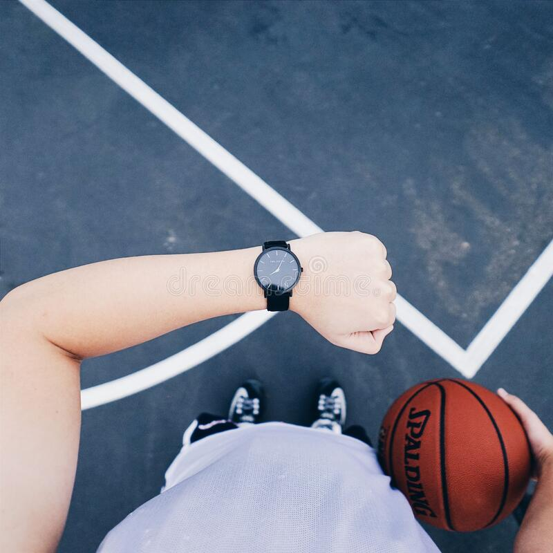 Person Wearing Black Round Analog Watch on Left Wrist While Holding Basketball on Right Hand stock photography