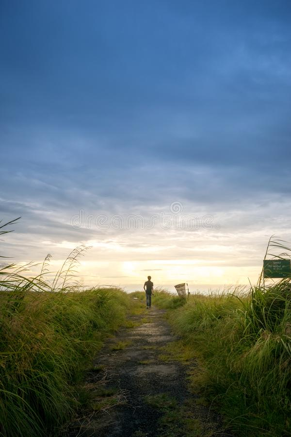 Person Wearing Black Shirt Walking Near Grass Field royalty free stock photo