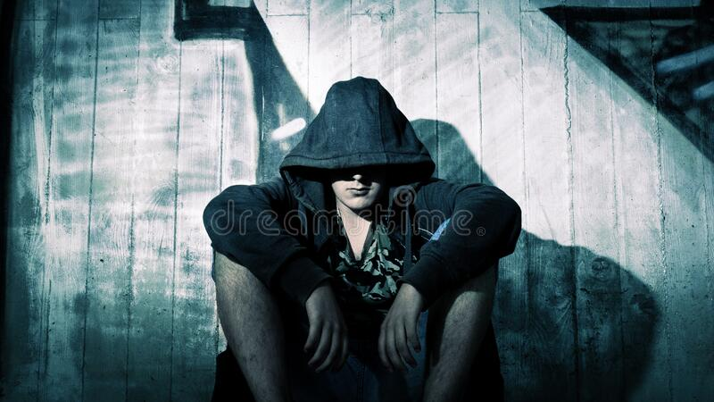 Person Wearing Black Zip Hoodie Sitting in Front of Gray Wooden Plank Wall during Nighttime stock photo
