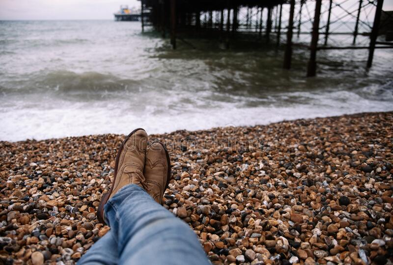Person Wearing Blue Denim Pants And Brown Boots Sitting On Brown And Black Stone In Front Of Body Of Water Free Public Domain Cc0 Image