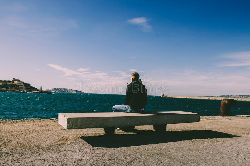 Person Wearing Blue Jeans Sitting on Bench stock photos