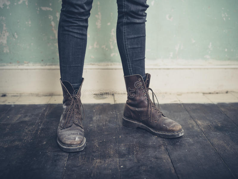 Person wearing boots standing in empty room royalty free stock photo