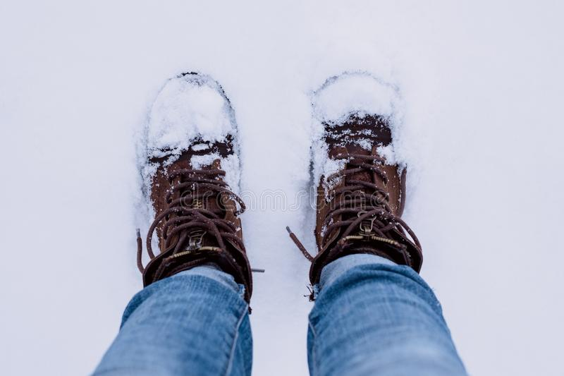 Person Wearing Brown Boots and Blue Denim Jeans Standing on Snow royalty free stock images