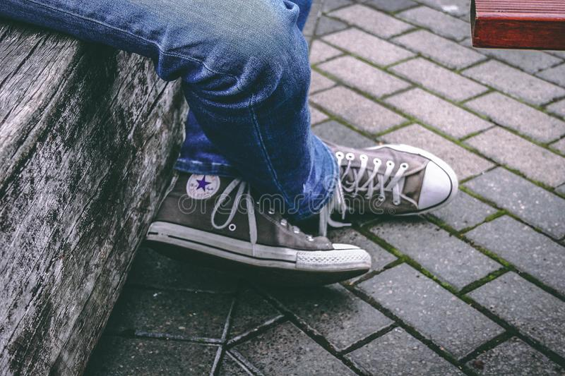 Person Wearing Brown Converse All-star High-top Sneakers And Blue Denim Jeans While Sitting On Bench Free Public Domain Cc0 Image